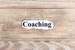 Coaching text on paper. Word Coaching on torn paper. Concept Image Stock Image