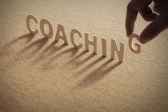 `coaching` wooden letters. The word `coaching` wooden letters on cork board background Stock Photos