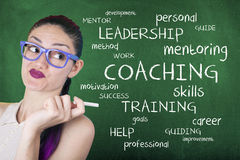 Coaching Word Cloud Concept. Female with coaching word cloud on chalkboard royalty free stock image