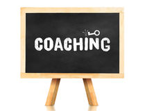 Coaching word and key icon on blackboard with easel and reflecti Royalty Free Stock Photography