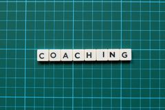 Coaching word made of square letter word on green square mat background. stock photography