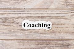 Coaching of the word on paper. concept. Words of coaching on a wooden background.  stock image