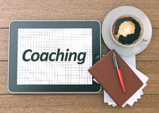 Coaching word on the screen of Digital Tablet PC. Workspace on w Stock Photos
