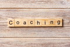 COACHING word written on wood block. COACHING text on table, concept royalty free stock images