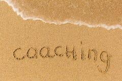 Coaching - written on sandy beach Stock Photography
