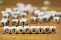Coaching written with wooden cubes royalty free stock photography