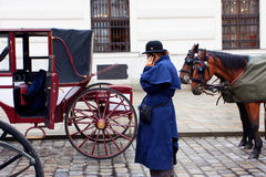 Coachman talk on a mobile phone near the horse-drawn carts Royalty Free Stock Photos