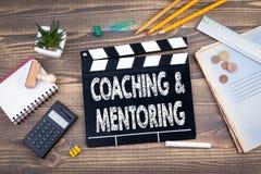 Coachning och mentoring filmclapper på ett träskrivbord arkivbilder