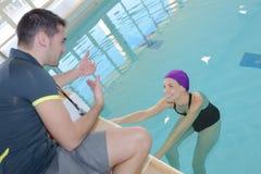 Coachtranier aan zwemmersmeisje bij pool die met athlet bespreken Royalty-vrije Stock Fotografie