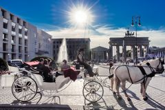 Coachwoman with horse-drawn carriage at Brandenburg Gate, Berlin, evening at Brandenburger Tor. Sun sending beams. royalty free stock photography