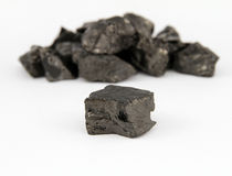 Coal. Piece of black coal with heap of coal on background royalty free stock photo