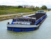 Coal barge in transit on canal. A coal barge on the Canal du Rhone a Sete in southern France royalty free stock photos