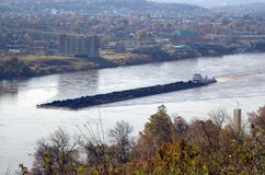 Coal barge on the move. Hilltop view of coal barge on the river stock image