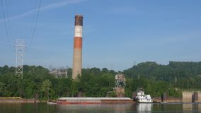 Coal Barge Passes A Factory Smokestack on the Ohio River. A coal barge passes a factory's tall smokestack on the Ohio River on a summer morning. Pittsburgh stock footage
