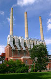 Coal burning power plant. A coal burning power plant surrounded by lawn and trees Royalty Free Stock Photos