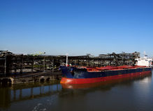 Coal Cargo Ship. A view of a cargo ship docked in a harbor hear a coal refinery royalty free stock photos