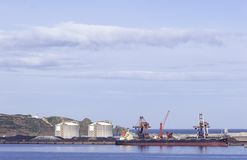 Coal cargo ship moored in port with lifting cargo cranes, ships and grain royalty free stock photo
