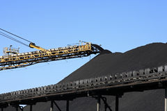Coal Conveyor Belt. A large yellow conveyor belt carrying coal and emptying onto a huge pile Royalty Free Stock Images