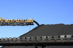 Coal Conveyor Belt. A large yellow conveyor belt carrying coal and emptying onto a huge pile Royalty Free Stock Photos