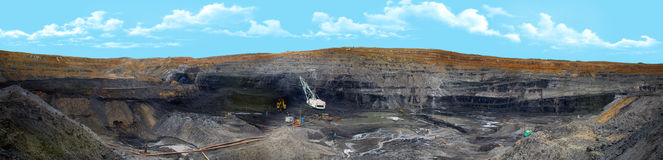 Coal cut panorama. Photograph of the existing coal mine. The machines working in the quarry are clearly visible Royalty Free Stock Photos