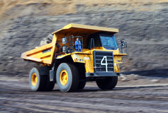 Coal dump truck at work. Motion panning shot of a monster truck on an open pit mine Stock Photos