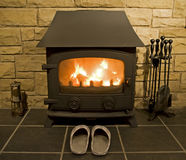 Coal fire and hearth at home. Coal fire with slippers on the hearth at home stock images