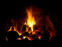 Coal fire. A roaring coal fire with glowing orange embers against a dark background Royalty Free Stock Photography