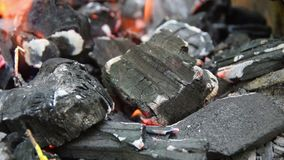 The coal in the fire smolders and burns. Close stock video footage