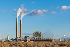 A coal-fired electrical power plant with smokestacks emitting plumes of smoke in the southwestern United States royalty free stock photo