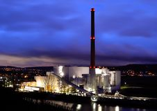 Coal-fired power plant at night with cloudy sky stock image