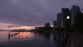 Coal Harbor Seawall Dawn, Vancouver. Sunrise on the seawall of Coal Harbor in downtown Vancouver. British Columbia, Canada stock video footage