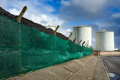Coal heap and fuel tanks. In the industrial place and sky Royalty Free Stock Photography