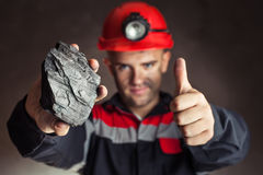 Coal miner with lump of coal. Coal miner showing lump of coal with thumbs up against a dark background Stock Photo