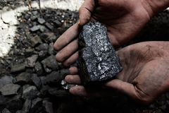 Coal miner in the man hands of coal background. Coal mining or e Stock Photo