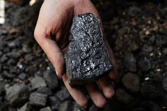 Coal miner in the man hands of coal background. Coal mining or e Stock Photos