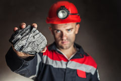 Coal miner showing lump of coal. Against a dark background Royalty Free Stock Photography