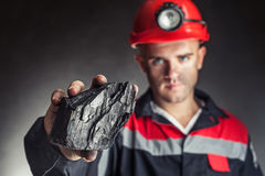 Coal miner showing lump of coal. Against a dark background Royalty Free Stock Images