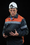 Coal miner showing lump of coal with thumbs up Stock Photo
