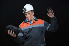 Coal miner showing lump of coal with thumbs up Stock Images