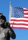 Coal Miner Statue and American Flag. A stone statue of a coal miner with american flag in background on blue sky Royalty Free Stock Images