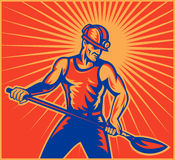 Coal miner worker at work. Illustration of a Coal miner worker at work with spade shovel front view  done in retro woodcut style with sunburst in background Stock Photo
