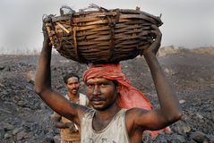 Coal mines in India. A labour carrying coal from the open mines in Jharia-India Royalty Free Stock Photos