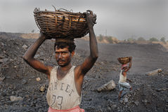 Coal mines in India. Labors carrying coal from the open mines in Jharia-India Royalty Free Stock Images