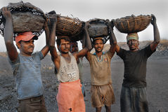 Coal mines in India. Labors carrying coal from the open mines in Jharia-India Stock Photo