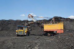 Coal mining. The dredge loads the truck coal. Royalty Free Stock Images