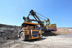 Coal mining. The dredge loads the truck coal. Stock Image