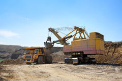 Coal mining. The dredge loads the truck ground. Stock Photography