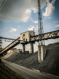 Coal mining industry. Coal mine heaps of coal on the mining site with cloudy sky Royalty Free Stock Image