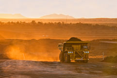 Coal mining truck in orange morning light. With dust behind and driver lit by reflection of the sun Royalty Free Stock Images
