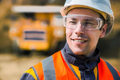Coal mining wokrer. Mine worker with huge truck on the background in open pit Royalty Free Stock Images